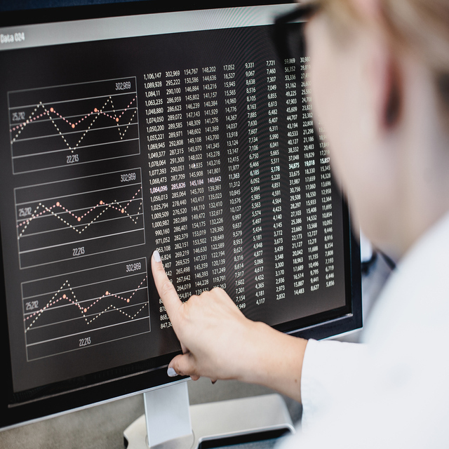 Female pharmacist analyzing data on a workstation.