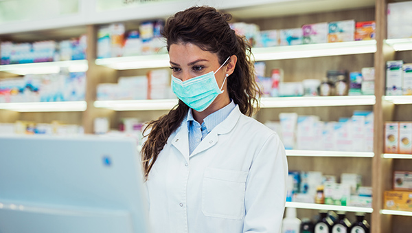 Female pharmacist with protective mask on her face working at ph